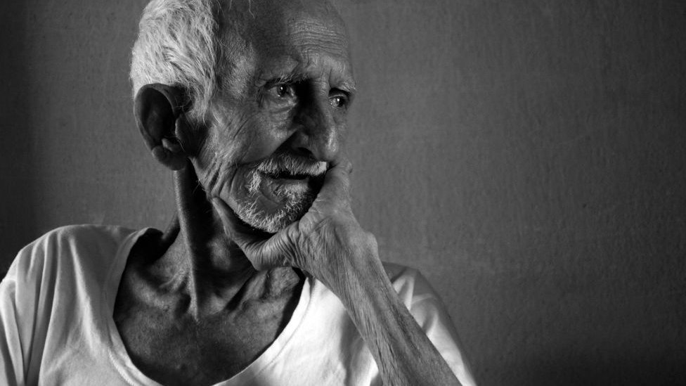 An old man looking outside with grief in the time of COVID-19 and hoping for those safe and pure days to come again, Nabagram, Hooghly, West Bengal, India.